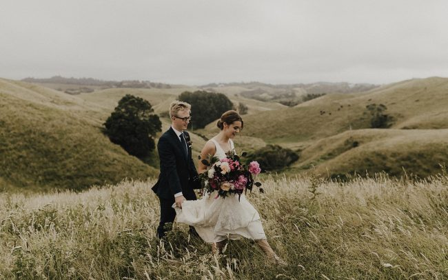 On My Hand Florist - Real wedding portfolio - Sasha and Josh - walking through a field with bride holding large bouquet