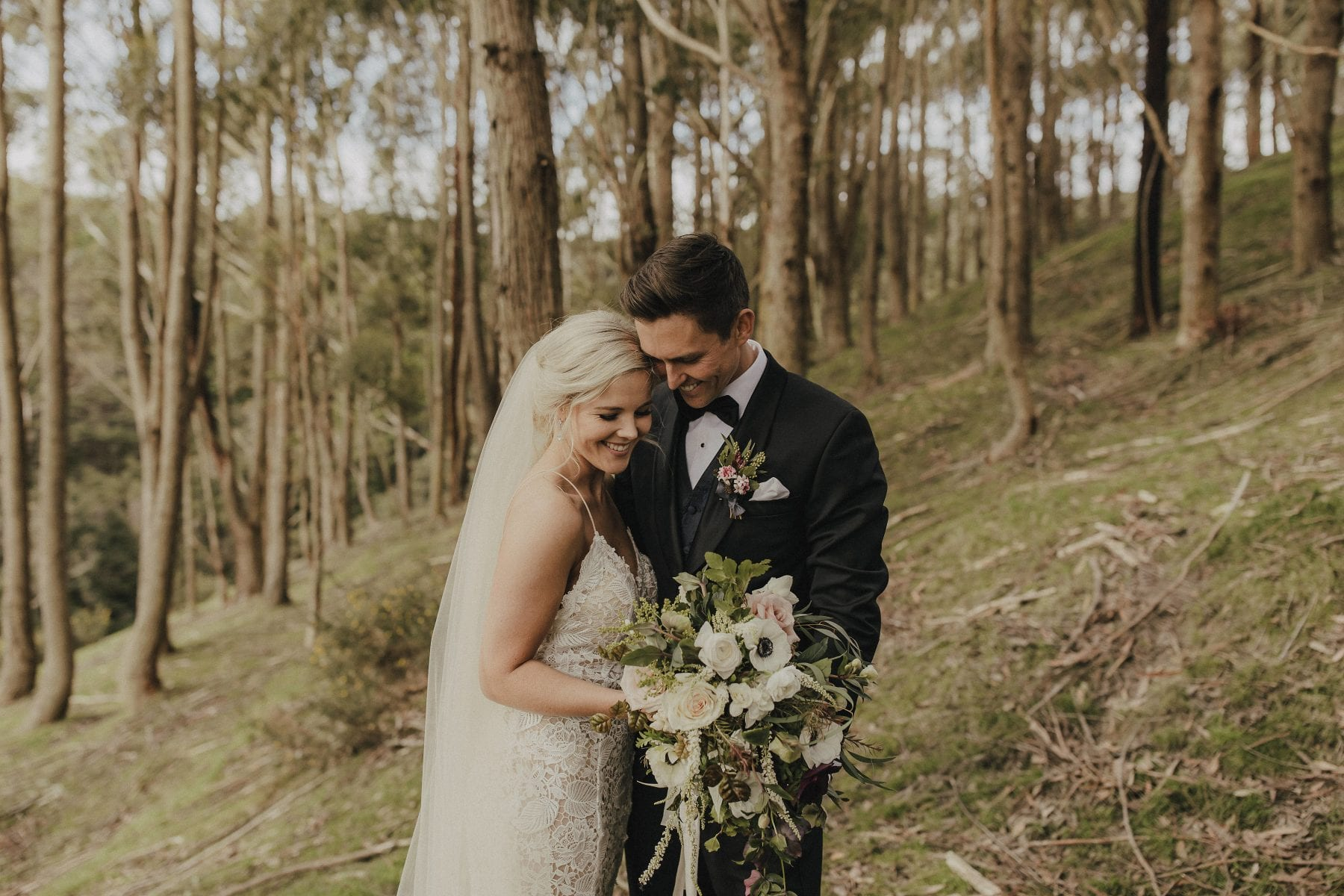 On My Hand Wedding flowers for real wedding - Gert and Trent in Kauri Bay Boomrock - bride and groom in woods looking at bouquet