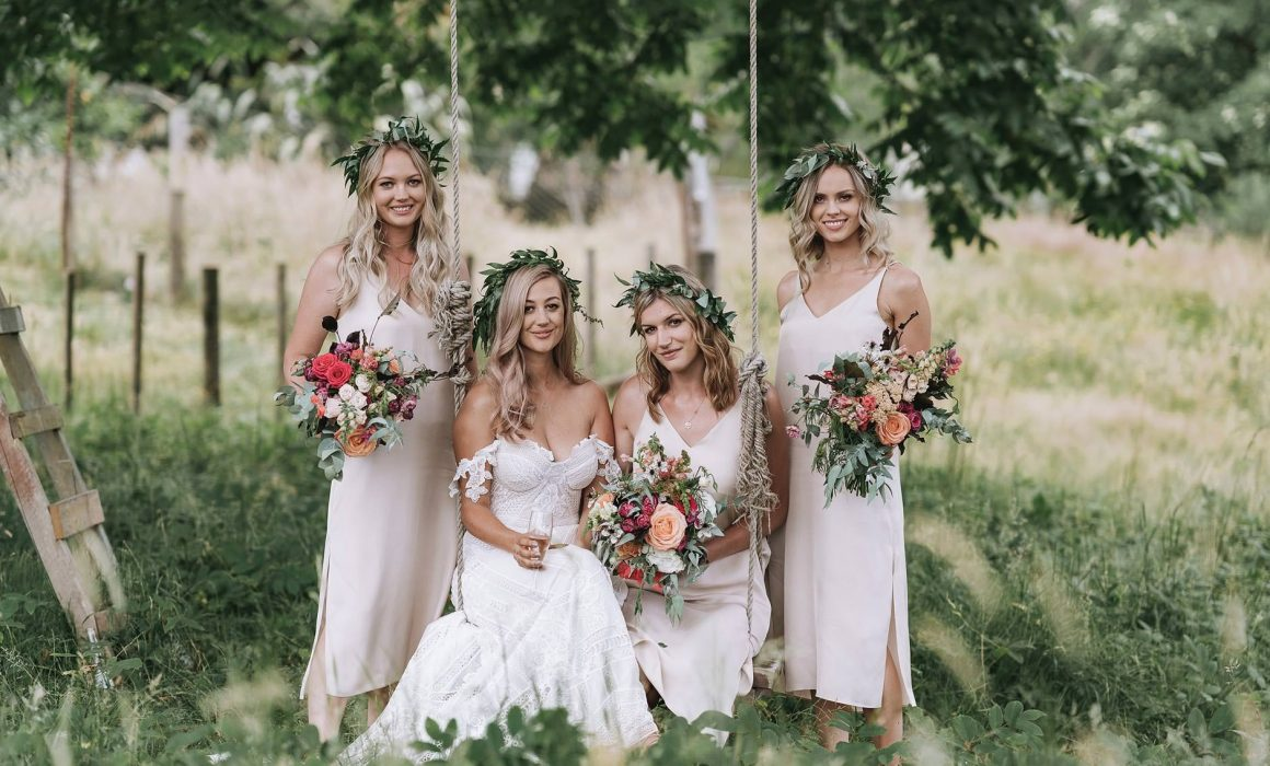 Real Wedding Lucy and Tom - bride and bridesmaids on wooden swing all holding bouquets created and styled by On My Hand, Tauranga