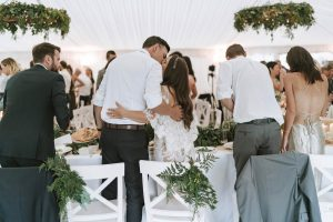 Real Wedding Hayley and Carl kiss at reception - flowers styled in reception marquee created by On My Hand florist in Tauranga