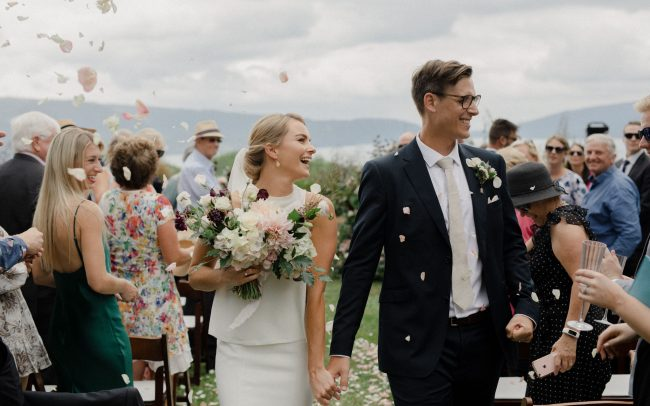On My Hand wedding flowers - real wedding with black barn elegance - bride and groom walk down aisle with confetti , bride holding bouquet