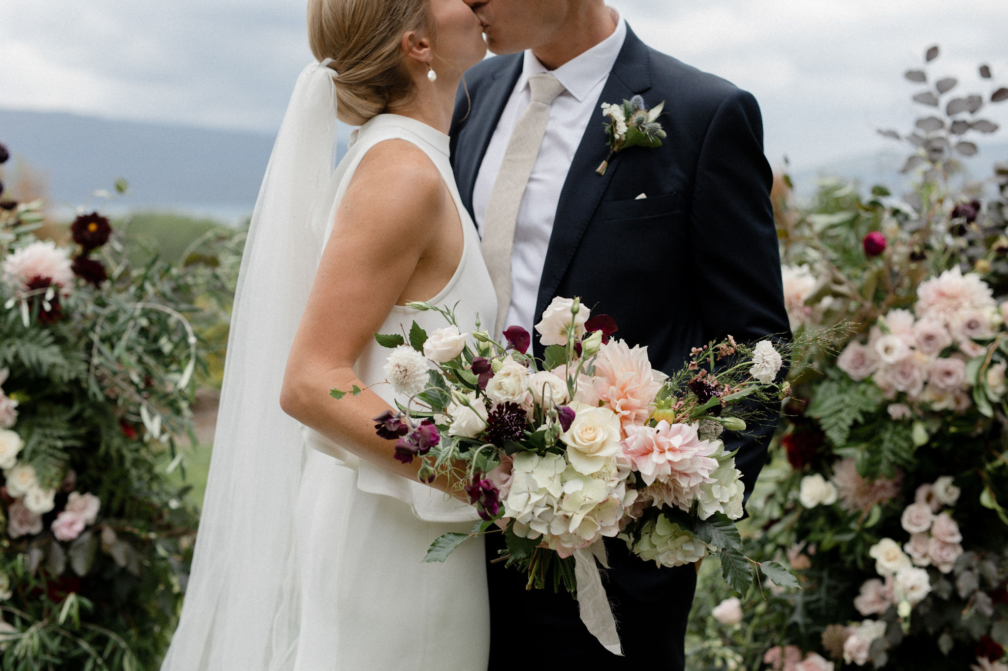 On My Hand wedding flowers - real wedding with black barn elegance - bride and groom kiss between floral arrangements, bride holding bouquet