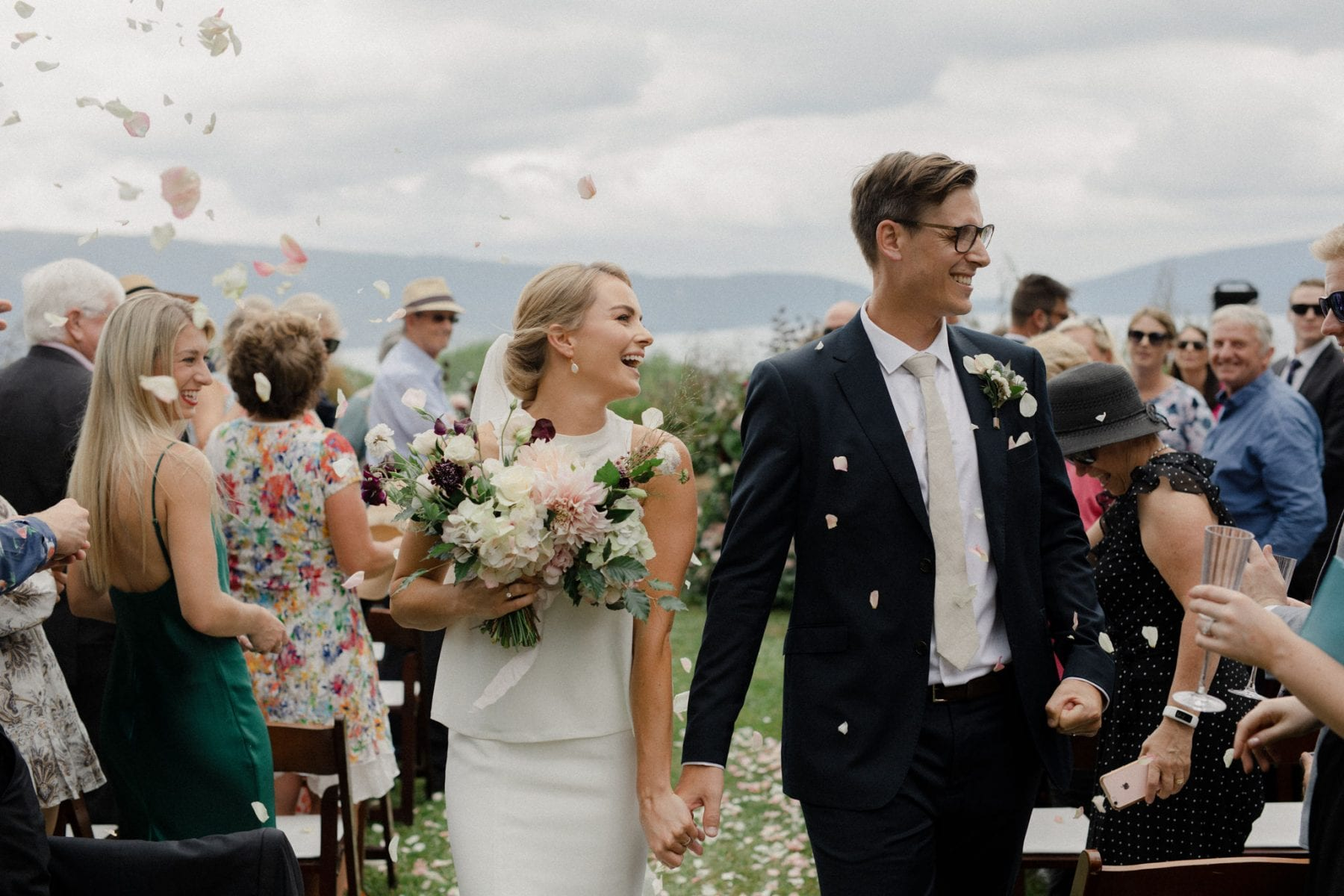 On My Hand wedding flowers - real wedding with black barn elegance - bride and groom walk aisle with bouquet and confetti
