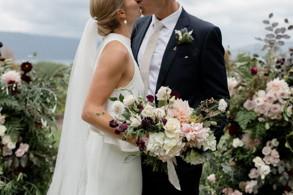 On My Hand wedding flowers - real wedding with black barn elegance - bride and groom kiss bridal bouquet front and centre