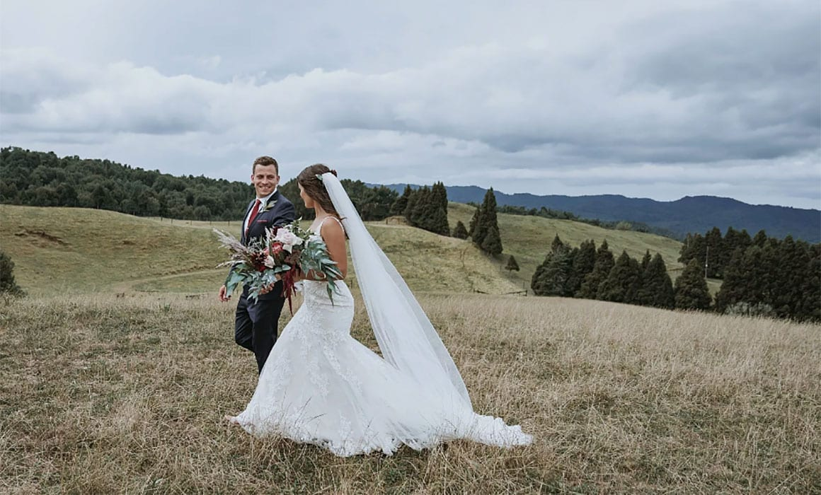 On My Hand - Kaimai Range Rustic Elegance - Bride and Groom walking through field bride with bouquet