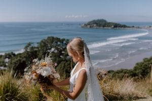 On My Hand Wedding Flowers for Ataahua ceremony and reception - bride with bouquets of fresh and dried florals