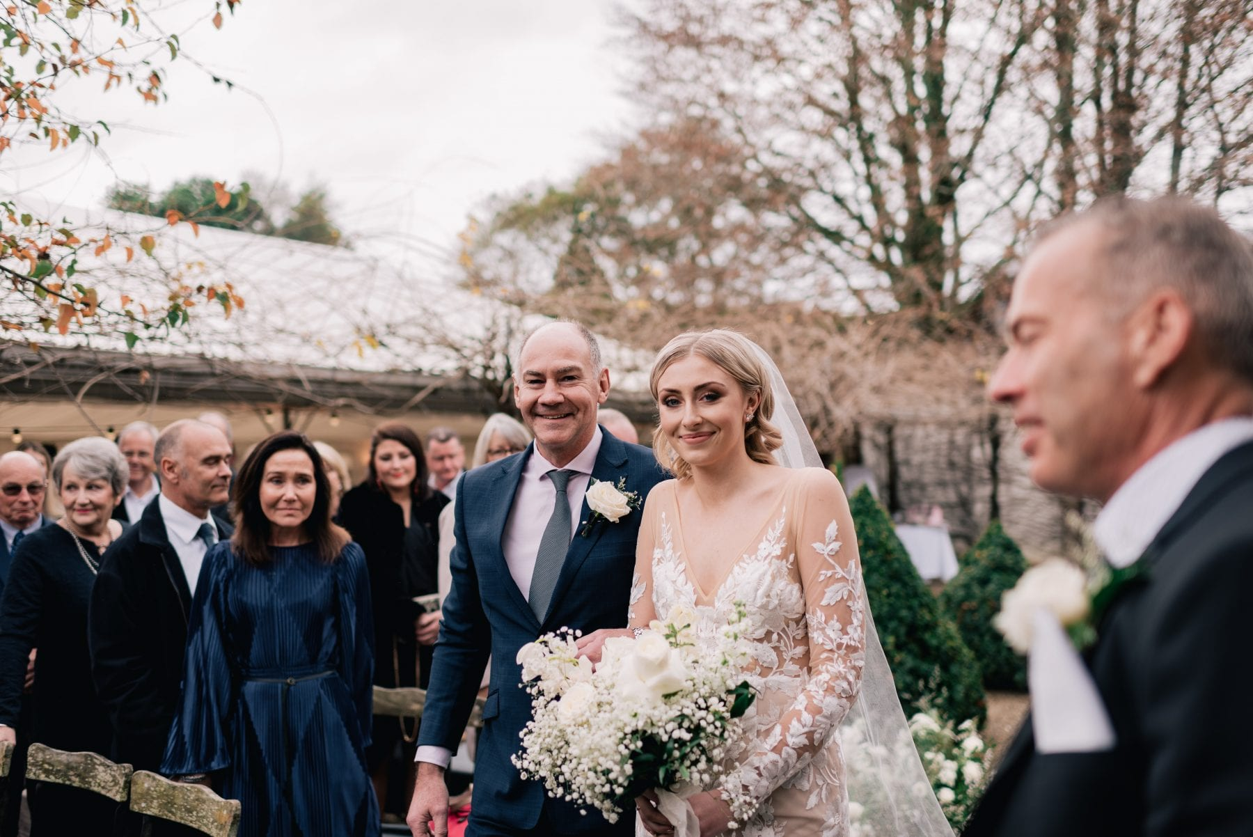 On My Hand Florist - Reuben and Hannah wedding - bride and groom at ceremony with bride holding beautiful white bouquet