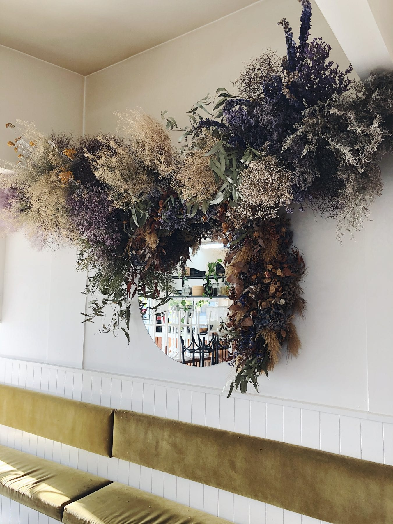 Stunning large floral arrangement around mirror from On My Hand Floral and Styling in Tauranga.
