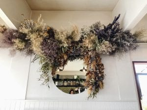 Stunning dried floral arrangement around mirror from On My Hand Floral and Styling in Tauranga.