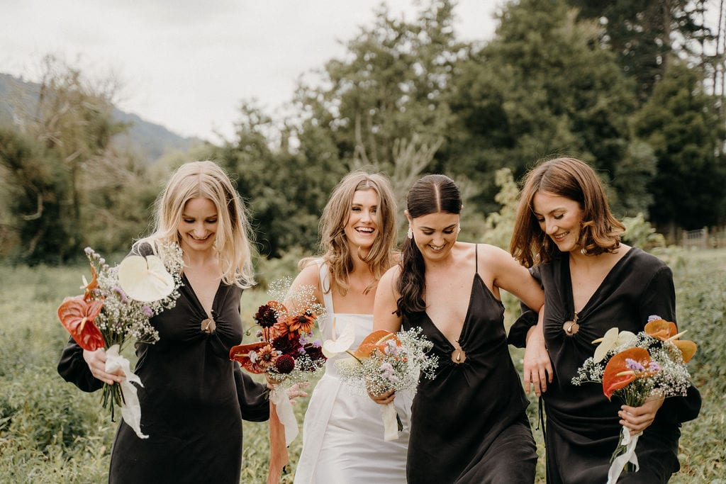 On My Hand Florist for Weddings and Events in Tauranga, Bay of Plenty. Lana and Wynn real wedding - bride and bridesmaids walk through field with bouquets.