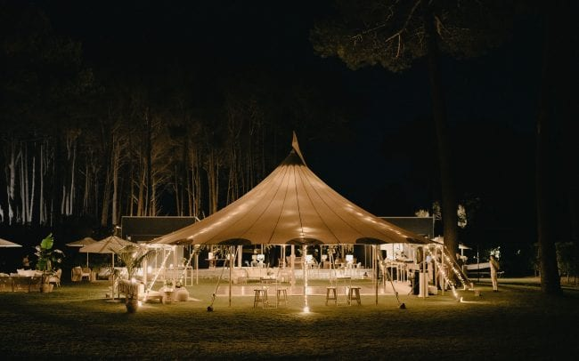 Real Wedding Nicole and Billy with wedding florals from On My Hand - open lit up tipi at nightime beautifully styled.