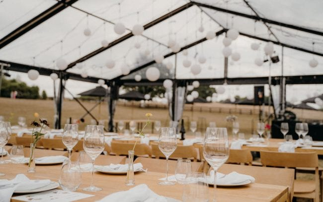 Real Wedding Lana and Wynn with wedding florals from On My Hand - clear marquee reception with wooden tables clean setting with simple flowers in vases.